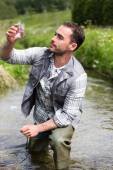 Biologist take a sample in a river in order to do some test — Stock Photo