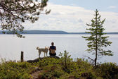 Girl with a dog sitting on a rock at the lake — Stock fotografie