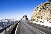 Asphalt road in mountain peak with snowfields — Stock Photo
