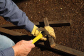 Hammering wood pieces for trellis — Stock Photo
