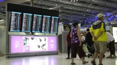 People near information board in international airport in Bangkok, Thailand — Stock Video