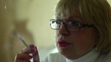Äldre kvinna med glasögon röka cigarett — Stockvideo
