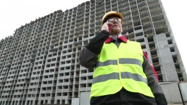 Master builder in hard hat with smartphone — Stock Video