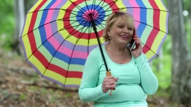 Woman with multicolored umbrella talking on telephone — Stock Video