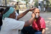 Street barber shaving a man using an open razor blade on a street in Kolkata — Stock Photo