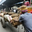 Постер, плакат: Hard working Indians pushing heavy load through streets Kolkata