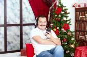 Mature man listening to music on headphones  near a New Year tre — Stock Photo