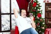 Mature man listening to music on headphones  near christmas tree — Stock Photo