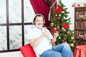 Man listening to music on headphones  near a christmas tree — 图库照片