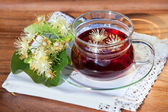 Cup with linden tea and flowers on wooden table — Stock Photo