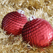 Two red Christmas baubles on golden tinsel — Stock Photo #56439179
