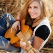 Beautiful girl playing the guitar in a wheat field — Stock Photo #55945363