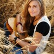 Beautiful girl playing the guitar in a wheat field — Stock Photo #55945365