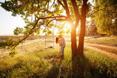 Young kissing couple under big tree with swing at sunset — Stock Photo
