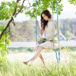 Young woman is swinging on a swing in summer forest. — Stock Photo #55981787