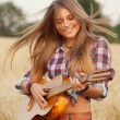 Beautiful girl playing the guitar in a wheat field — Stock Photo #55984969