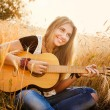 Beautiful girl playing the guitar in a wheat field — Stock Photo #55985967