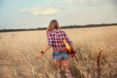 Slender girl with a guitar running through the wheat field — Stock Photo