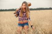 Beautiful girl with guitar goes on wheat field — Stock Photo