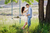 Young kissing couple under big tree with swing — Stock Photo