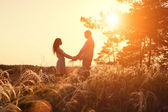 Young couple holding hands. In nature sunrise — Stock Photo