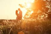 Loving couple kissing at sunset — Stock Photo