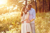 Young couple in love at sunset in the field — Fotografia Stock