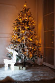 A lighted Christmas tree with presents underneath in living room — Zdjęcie stockowe