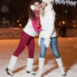 Two beautiful girls ice skating outdoor on a warm winter night — Foto Stock #61752339