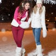 Two beautiful girls ice skating outdoor on a warm winter night — Stockfoto #61752377