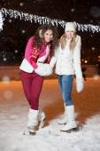 Two beautiful girls ice skating outdoor on a warm winter night — Stock Photo