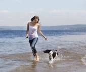 Girl and dog running on a beach — Stock Photo