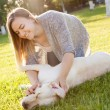 Beautiful woman playing with her dog Labrador retriever — Stock Photo #77136045