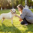 Beautiful woman playing with her dog Labrador retriever. — Stock Photo #77136399