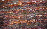 Old grunge brick wall background covered with some paint and graffiti — Foto de Stock