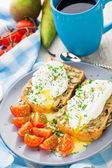 Sandwich with poached egg and cherry tomatoes — Stock Photo