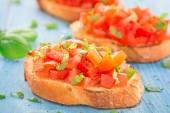 Italian tomato bruschetta with basil — Stock Photo