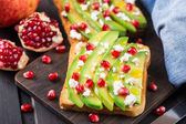 Avocado sandwich with feta and pomegranate — Stock Photo