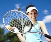 Girl standing with tennis equipment — Stock Photo