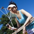 Girl rests on a tennis net — Stock Photo #52121683