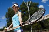 Girl standing near tennis grid on the sky — Stock Photo