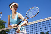 Girl rests on a tennis net — Stockfoto