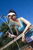 Girl rests on a tennis net — Stock Photo