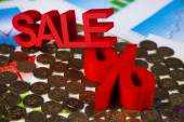 Sale sign on heap of coins — Stock Photo