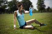 Sporty woman with bottle of drink — Stock Photo