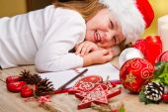 Funny girl in Santa hat writes letter to Santa near christmas de — Stock Photo
