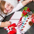 Funny girl in Santa hat writes letter to Santa near christmas decoration — Stock Photo #57697755