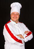 Handsome chef posing against black background  — Stock Photo