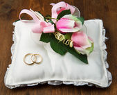 Wedding rings with roses on bridal pillow — Stock Photo