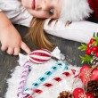 Funny girl in Santa hat writes letter to Santa near christmas decoration — Stock Photo #59326847